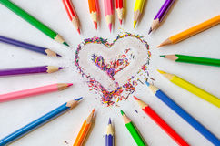 Multicolored pencils with heart of shavings. Wooden colorful pencils with sharpening shavings in form of heart. Beautiful love concept Royalty Free Stock Image