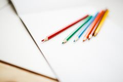 Multicolored pencils lying on a white table Stock Photos