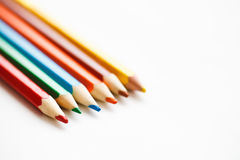 Multicolored pencils lying on a white table Royalty Free Stock Images