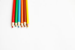 Multicolored pencils lying on a white table Stock Image