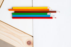 Multicolored pencils lying on a white table Stock Images