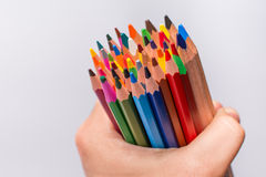 Multicolored pencils in the man hand on a white background. Back to school concept. Stock Images