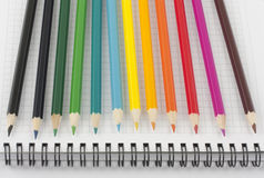 Multicolored pencils on opened notebook. Multicolored pencils on page of opened spiral notebook Stock Image