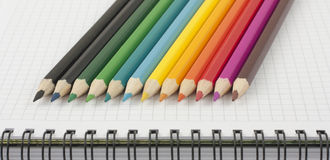 Multicolored pencils on opened spiral notebook. Multicolored pencils on page of opened spiral notebook Stock Images