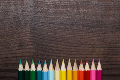 Multicolored pencils over brown wooden table Stock Photography