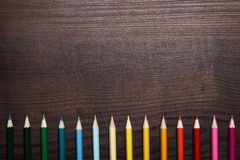 Multicolored pencils over brown wooden table Stock Photos