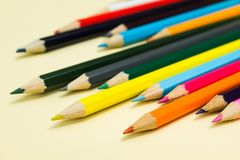 Multicolored pencils on a pastel yellow background.  royalty free stock photos