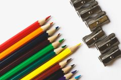 Multicolored pencils and sharpeners on the white surface. Macro top wiev Royalty Free Stock Photos