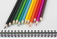 Multicolored pencils on spiral notebook stock photos
