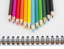 Multicolored pencils on spiral notebook Royalty Free Stock Photos