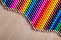 Multicolored pencils in wave form on wooden table Stock Photos