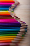 Multicolored pencils in wave form on wooden table Stock Images