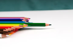 Multicolored pencils on the white paper. Back to school. Copy space. Top view Stock Photos