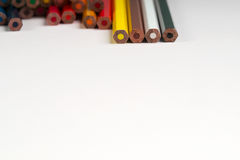 Multicolored pencils on the white paper. Back to school. Copy space. Top view royalty free stock photo