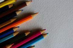Multicolored pencils on white textured paper background. Art creation and school concept Stock Images