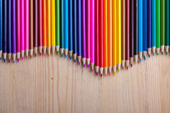 Multicolored pencils on wooden table, top view. Stock Photo