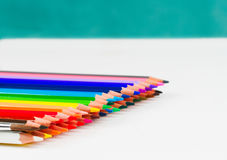 Multicolored pensils in the box on the white paper. Stock Image