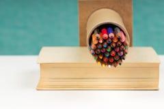Multicolored pensils in het vakje op het boek Royalty-vrije Stock Afbeelding