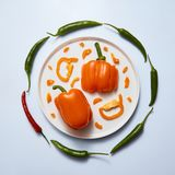 Plate with sliced colored peppers on a light background royalty free stock photos