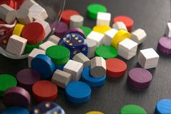 A multicolored pile consisting of dice and wooden chips. Close-up Stock Photo