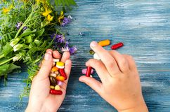 Multicolored pills, capsules in hand on blue background. Studio Photo royalty free stock images