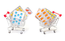 Multicolored pills packs in shopping cart Royalty Free Stock Photos