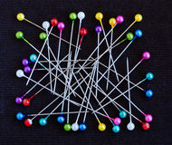 Multicolored pins over black background Royalty Free Stock Photos