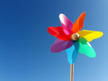 Multicolored pinwheel in front of blue sky stock photos