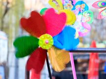 Multicolored pinwheel toy with flower on beach royalty free stock photography