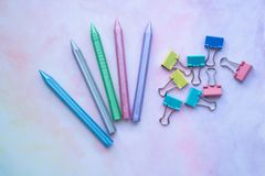 Multicolored plastic crayons and paper-clips from top view on pastel watercolor background. royalty free stock images