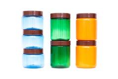 Multicolored plastic kruiken van sinaasappel, groen en blauw op een witte achtergrond, polypropyleen stock fotografie