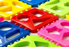 Multicolored plastic puzzle. Background of multi-colored plastic puzzle elements. View at an angle. Early development of children. The study of geometric shapes Stock Photography