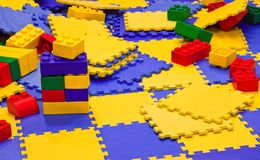 Multicolored plastic toy bricks and carpets Stock Photography