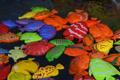 Multi-colored artificial fish for children`s fishing in water royalty free stock images