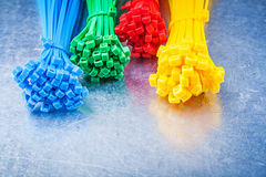 Multicolored plastic tying cables on scratched metallic backgrou Royalty Free Stock Images