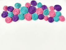 Multicolored plasticine clay, spiral dough arrange curve shape. Multicolored plasticine clay are curled into a spiral placed on a white background, pink blue royalty free stock image
