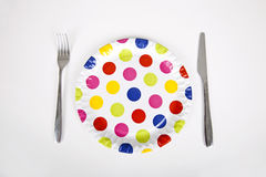 Multicolored plate with polka dots and cutlery against white background Stock Image