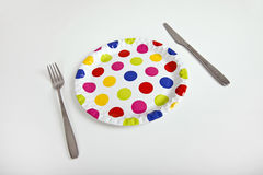 Multicolored plate with polka dots and cutlery over white background Stock Photo