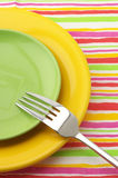 Multicolored plates and fork Stock Photos