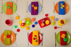 Multicolored plates and linen napkins with knitted decor. Table royalty free stock images