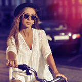 Multicolored portrait of a beautiful woman on a vintage bike Stock Photos