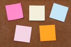 Multicolored post-it-notes sticks on wooden board Stock Images