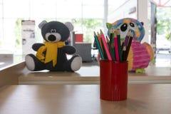 Multicolored potloden in een rode kop op een houten lijst Op de achtergrond - het speelgoed van kinderen De hoek van kinderen - e stock foto