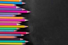 Multicolored potloden op een zwarte school schepen met een plaats voor een inschrijving in stock foto