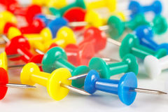 Multicolored pushpins on white desktop closeup Stock Photography