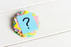 Multicolored question marks written reminders tickets on white wooden background.  Royalty Free Stock Image