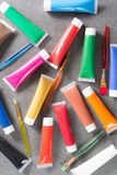 Multicolored acrylic paints tubes set with five colorful brushes Royalty Free Stock Image