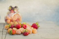 Multicolored raspberries in a glass jar with strawberries on background. Black, red, yellow raspberries in a glass jar with strawberries on a old wooden Royalty Free Stock Images
