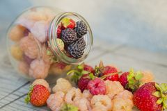 Multicolored raspberries in a glass jar with strawberries on background Stock Photo