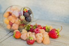 Multicolored raspberries in a glass jar with strawberries on background. Black, red, yellow raspberries in a glass jar with strawberries on a old wooden Stock Image